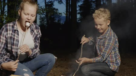 костер : Teenagers preparing marshmallows on wooden sticks on bonfire in forest hike. Girl and boy teenagers eating marshmallows on evening picnic in summer forest