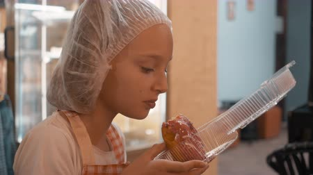 pastelaria : Teenager girl in disposable hat and kitchen apron eating donuts. Cook girl eating fresh donuts in pastry shop. Portrait Baker girl in culinary clothes