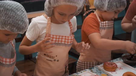 piekarz : Children topping donuts on cooking master class in culinary school. Teenagers cooking donuts with colorful glaze in bakery master class. Cooking lesson in school Wideo