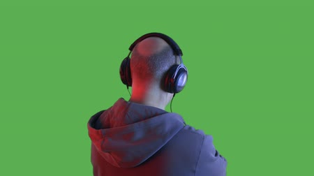 auricolari : Back view of man in headphones listening music in studio. Rear view of middle aged man in hoodie, sunglasses and headphones standing with crossed arms and listening music on transparent alpha channel