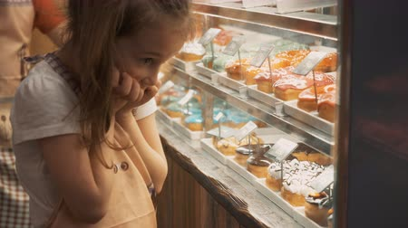 сладость : Adorable happy children looking and pointing at pastries in showcase. Close-up view of cute excited kids choosing candies and sweets in bakery display case