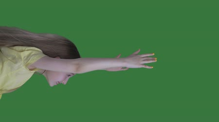 flying witch : Teenager girl with long hair flying in sky on green background. Young girl flying like witch on green chroma key screen. Alpha channel, keyed green screen Stock Footage