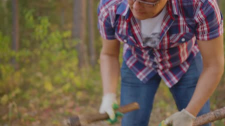 hatchet : Adult man chopping woods with axe in summer forest. Lumberman in checkered shirt using axe for chopping firewood in summer woodland Stock Footage