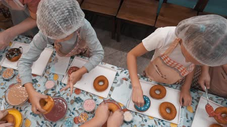 rosquinhas : Top view kids cooking donuts with colorful glaze on bakery master class. Overhead children preparing doughnut in culinary class in bakery shop. Culinary education for girls Stock Footage