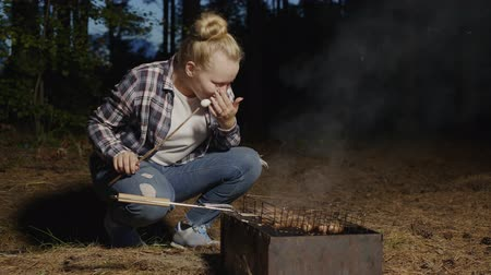 torrefação : Young girl eating hot marshmallows from wooden sticks fried on barbeque fire. Girl teenagers roasting marshmallows barbeque bonfire on forest picnic at evening