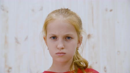 malice : Portrait serious girl teenager frowning forehead in light studio. Close up face angry girl looking displeased to camera. Negative facial emotions of young people Stock Footage