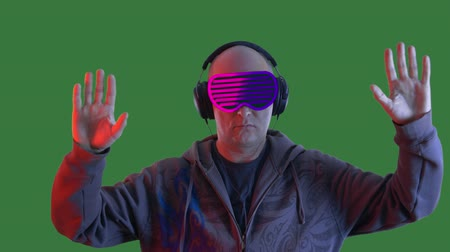 tenso : Adult man wearing virtual reality headset waving hands on green background. Bald man watching vr goggles and moving hands on chroma key background. Alpha channel, keyed green screen