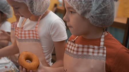 piekarz : Young boy licking finger while cooking donuts in culinary school. Boy on cooking cap and apron preparing donuts on cooking master class in bakery shop. Culinary education