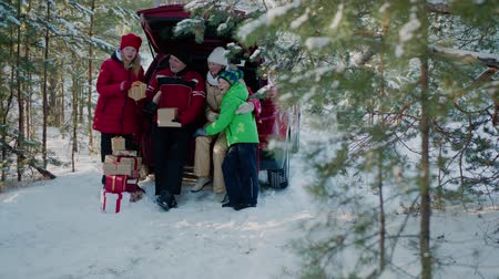 father christmas : Happy family looking New Year gift in car trunk in winter forest. Mom, dad, son and daughter in red Christmas hat having fun together dog in snowy woodland at winter holiday Stock Footage