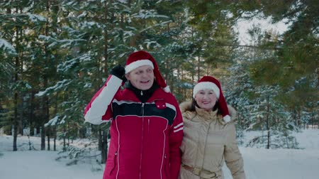świety mikołaj : Winter couple in Christmas hat walking on snowy forest. Couple in love man and woman walking on snowy woodland at winter vacation. New Year Santa walks in forest