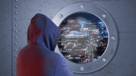 devise : Man in headphone and black glasses looking to aircraft spaceship window flying over night city. Man in hood looking to camera on window. Night city landscape in aircraft window Stock Footage
