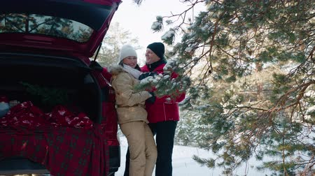 gyengéd : Happy couple in love laughing in snowy forest on red car background at winter walk. Smiling man and woman having fun together in winter forest