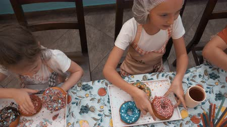 preparado : Hungry teenagers eating donuts with colorful glaze on culinary kitchen. Happy children in cook hat and apron eating donuts prepared on culinary master class in bakery school