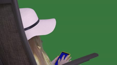áttekinthetőség : Girl in sun hat using smartphone. Beautiful teenage girl in straw hat sitting on beach chair and browsing via cell phone on transparent background with alpha channel Stock mozgókép