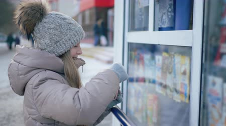 кошелек : Teenager girl buying ice cream in street kiosk on winter walk. Happy girl buyer paying money from wallet for winter drink in street shop on walk