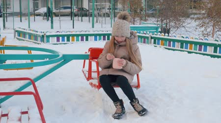кошелек : Teenager girl found wallet on snowy children ground at winter walk. Young girl taking wallet lying on snow on winter playing ground in city