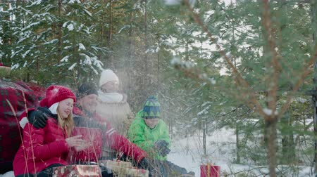 kâr : Happy family with presents throwing snow in winter forest. Happy parents and children sitting together with christmas gifts and dog in beautiful winter forest Stok Video