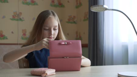 кошелек : Young girl taking cash from wallet sitting at table in cozy office room. Teenager girl putting paper money in new wallet at home office table