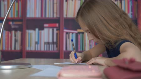 книжный шкаф : Schoolgirl writing by pen on paper sheet on bookshelf background. Student girl writing homework in cozy office on bookcase background in home Стоковые видеозаписи