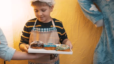 bandeja : Adorable happy little boy holding tray with delicious sweet doughnuts. Cute little boy in hat and apron holding tasty donuts after culinary master class