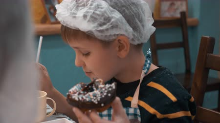 застекленный : Little boy eating doughnut and drinking with straw. Close-up view of cute preteen boy eating delicious chocolate donut and drinking from cup after culinary master class
