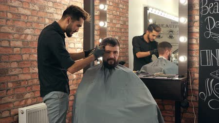 beard trim : Barber shaving bearded man with electric razor in barber salon. Bearded man getting trimming beard with shaver in male salon. Stylist shaving hipster man