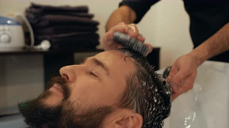masaż twarzy : Male hairdresser massaging head to client special brash. Portrait bearded man washing head with shampoo in barber shop. Male stylist washing hair in barber salon. Head massage