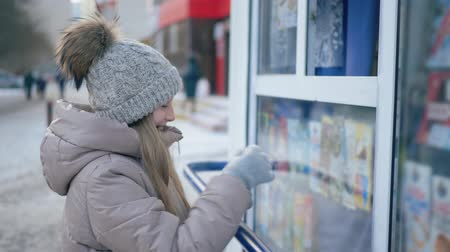 кошелек : Side view of smiling teenage girl buying sweets in kiosk shop. Cute cheerful teen girl in knitted hat and warm clothes holding wallet and looking at showcase at wintertime