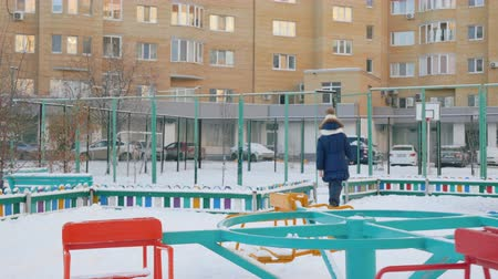 gebreid : Back view of girl walking near carousel from playground. Rear view of child in winter jacket and knitted hat walking on snow-covered street in city