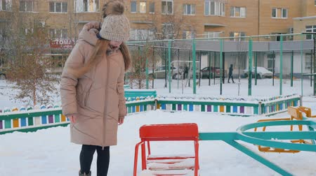 кошелек : Cute happy girl walking on street and finding wallet on playground. Cheerful teenage girl in warm clothes walking outdoor and finding wallet with money in snow at winter day