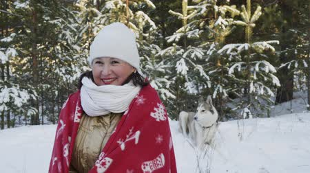 ladin : Smiling woman wrapped in Christmas plaid on cold weather winter walk with dog in snowy forest. Happy woman warming in red plaid on forest walk at New Year holiday together dog