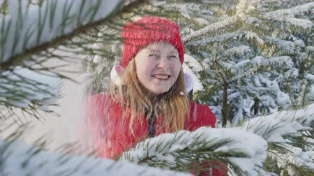 ladin : Happy young woman blowing to fluffy snow on hands on winter forest. Smiling girl teenager throwing snow in winter woodland on snowy trees background on New Year walk