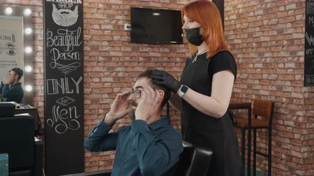 grzebień : Bearded man talking with male stylist in barber shop. Client in male beauty salon talking with woman hairdresser. Hair stylist working with customer in male barber salon Wideo