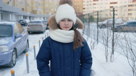 knitted : Upset girl crying and walking on snow-covered street. Sad teenage girl in knitted hat, scarf and winter jacket crying and walking on pathway in city at wintertime Stock Footage