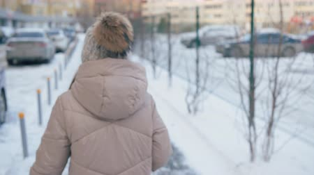 zajímavý : Girl walking on street and turning to look back at winter day. Beautiful teenage girl with ice cream walking on snow-covered street and looking over shoulder
