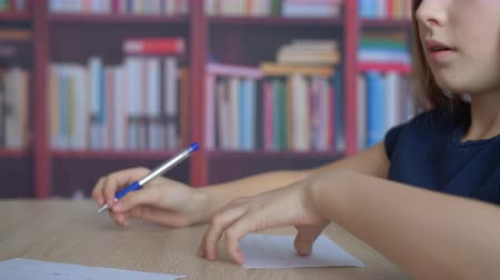 close cropped : Close-up view of cute focused girl writing on paper at desk. Cropped shot of adorable child writing notes, holding papers and going away at home Stock Footage