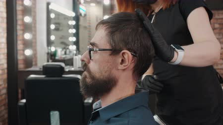 bigode : Cropped shot of barber in gloves touching head of stylish man. Hairdresser working with handsome bearded man in eyeglasses sitting in chair at barbershop, side view Stock Footage