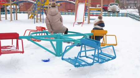 карусель : School girls turning on carousel swing on snowy playground at winter vacations. Teenager girl friends riding on merry go round on children playground at winter walk Стоковые видеозаписи