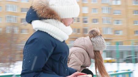 поворотный : Laughing girl teenagers rotating on carousel swing on snowy playground at winter walk. Point of view girl friends turning on merry go round on children playground at winter
