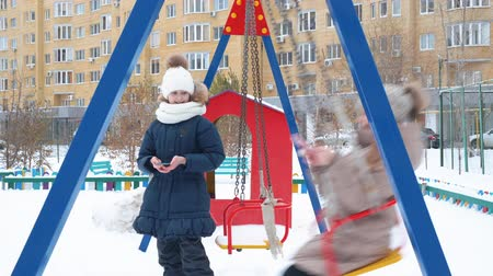 поворотный : Teenager girl swinging on snowy playground at holiday vacations in winter city. Happy girl friends swinging on swing on children playground at winter walk