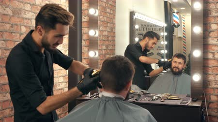 beard trim : Young barber with hair clipper trimming male client in barbershop. Smiling young hair stylist holding electric hair trimmer and grooming bearded male client looking at reflection in mirror