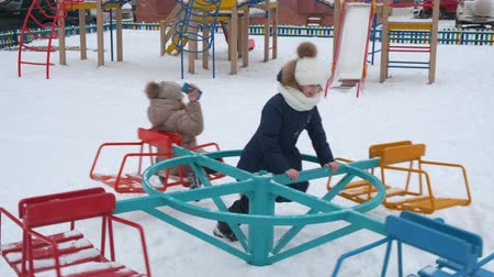 nastolatki : Happy cute girls playing together on carousel at wintertime. Adorable cheerful teenage girls in winter clothes having fun on merry-go-round at snow-covered playground