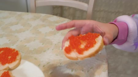 tomar : Close up female hand taking sandwich with red caviar. Face teenager girl biting bread sandwich with red caviar
