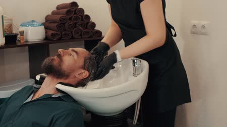 szampon : Hairstylist washing male hair with shampoo in barber salon. Hairdresser hand wash male head before cut. Male hair care in barbershop salon