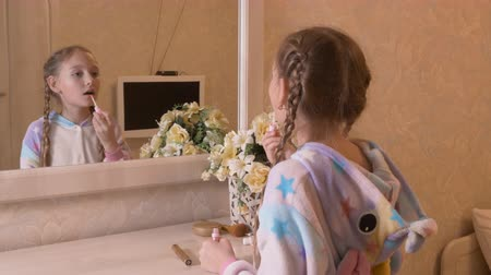 szminka : Teenager girl making lips makeup front mirror in white light beige bedroom. Young girl in pajamas unicorn using liquid lipstick for makeup front bedroom mirror, back view Wideo