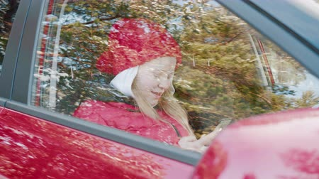 cappello rosso : Cross window view Young woman using mobile phone inside red car. Carefree girl in red hat and jacket typing smartphone inside car on passenger seat, outdoor view to window Filmati Stock