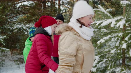 noel ağacı : Friendly family holding hands walking play ring around pine tree in snowy woodland at winter vacation. Mom, daughter, son and dad round dance near Christmas tree in winter forest