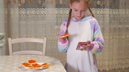 infância : Cute little girl using smartphone and eating red caviar at home. Adorable teenage girl standing in kitchen with smartphone in hand and eating toast with delicious caviar