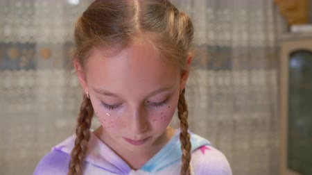 descontente : Close-up view of dissatisfied little girl looking at camera at home. Portrait of displeased girl with tinsels on face and braids looking at camera indoors Stock Footage