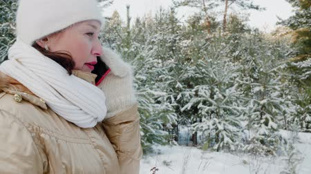 天候 : Woman talking by smartphone and walking in winter forest. Side view of beautiful smiling middle aged woman talking by cell phone while walking between snow-covered trees in forest at wintertime 動画素材